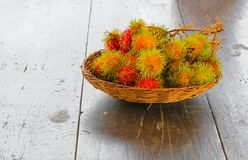 Rambutans fruit in basket on a wood desk background.  Royalty Free Stock Photos
