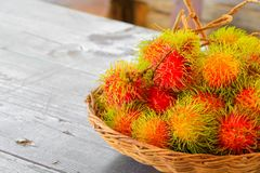 Rambutans fruit in basket on a wood desk background.  Royalty Free Stock Photography