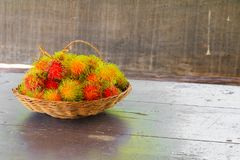 Rambutans fruit in basket on a wood desk background.  Stock Images