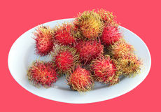 Rambutans on plate. Isolated on pink background Royalty Free Stock Photo
