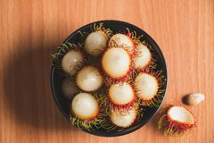 Rambutans. Top view of rambutans in the plate on the  brown wood table Royalty Free Stock Images