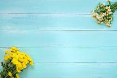 Rame gjorde av vita lösa blommor, och den gula krysantemumet blommar på blå träbakgrund arkivfoto