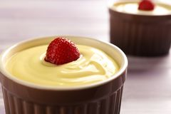 Ramekin with tasty vanilla pudding on table, Royalty Free Stock Images