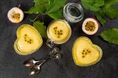 Ramekin tres con crema batida de la fruta de la pasión en el fondo oscuro, superior foto de archivo