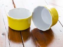 Ramekins amarelos na tabela de madeira Imagens de Stock