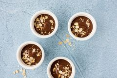 Ramekins filled with homemade chocolate pudding, decorated with roasted almond slivers, on light blue concrete background with. Copy space. Top view royalty free stock image