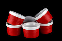 Ramekins rossi e bianchi isolati sul nero fotografia stock