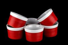 Ramekins rouges et blancs d'isolement sur le noir Photo stock