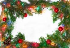 Ramen av granfilialer och julkortkortet tänder Royaltyfri Bild