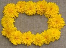 Ramen av guling blommar mot en bakgrund av den grova torkduken Arkivbild