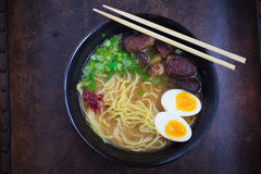 Ramen in bowl. Ramen soup in bowl with egg, green onion, chili paste and shiitake mushrooms with chopsticks Stock Photo