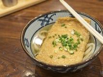 Ramen- eller japannudlar som överträffar med den djupa stekte tofuen och salladslökar i klar soppa fotografering för bildbyråer