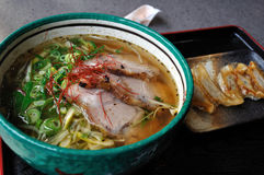 Ramen with gyoza. A bowl of Japanese Ramen with Chashu (roast pork) and spring onions in a clear soup. A side dish of Gyoza (pot stickers/dumplings) is also stock images