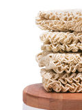 Ramen instant raw noodles staked on wooden plank Royalty Free Stock Photos