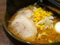 Ramen japoneses com fatias da carne de porco, grãos no caldo grosso Consiste em macarronetes do trigo do Chinês-estilo serviu em  foto de stock