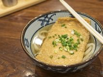 Ramen o tallarines japoneses que rematan con el queso de soja y cebolletas fritos en sopa clara imagen de archivo