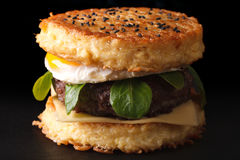 Ramenhamburger met rundvlees en eierenmacro op een zwarte achtergrond stock afbeelding
