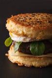 Ramenhamburger met rundvlees en eierenmacro op een zwarte achtergrond vert royalty-vrije stock fotografie