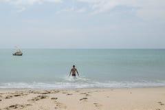 Man going to swim at remote beach Stock Photos