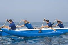 Rameurs barbotant le canoë de tangon dans la course image stock