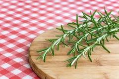 Rami dei rosmarini sul bordo di legno della cucina Ingredie dei rosmarini Immagini Stock