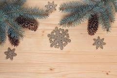Rami del pino, dei coni e dei fiocchi di neve su una superficie di legno Fotografia Stock