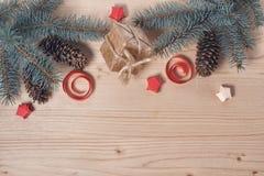 Rami del pino e dei coni su una decorazione di legno e di carta Fotografie Stock