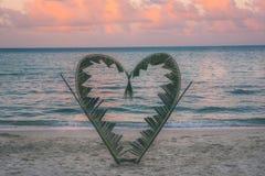Rami della palma legati nella forma di un cuore sulla spiaggia Immagini Stock Libere da Diritti
