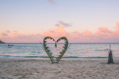 Rami della palma legati nella forma di un cuore sulla spiaggia Fotografie Stock