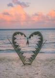 Rami della palma legati nella forma di un cuore sulla spiaggia Immagini Stock