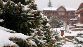 Rami di albero di caduta dell'abete della neve, cottage di legno su fondo Precipitazioni nevose pesanti alla stazione sciistica d archivi video