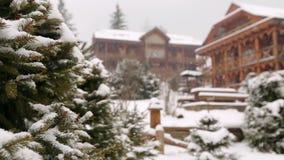 Rami di albero di caduta dell'abete della neve, cottage di legno su fondo Precipitazioni nevose pesanti alla stazione sciistica d video d archivio