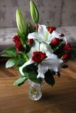 Ramillete de flores en el florero lirio y rosas rojas Fotografía de archivo libre de regalías
