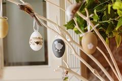 Ramita de la primavera con los huevos de Pascua para el arreglo del día de fiesta en el interior casero Fotos de archivo