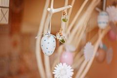Ramita de la primavera con los huevos de Pascua para el arreglo del día de fiesta en el interior casero Imagenes de archivo