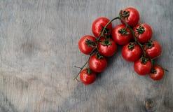 Ramita de los tomates de cereza red delicious frescos en una vieja etiqueta de madera Imagen de archivo