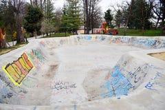 Ramnicu Valcea, Roemenië - 02 04 2019 - het schaatsen het ontwerpskateboard die van het vleetpark skatepark leeg beton met graffi stock afbeelding