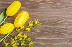 Ramo amarillo de los tulipanes en el fondo de madera marrón, espacio de la copia Imagen de archivo
