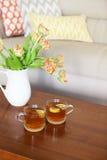 Ramo anaranjado hermoso de los tulipanes con dos tazas de té Foto de archivo