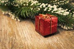 Ramo attillato con neve, contenitore di regalo rosso su legno d'annata Fotografia Stock Libera da Diritti