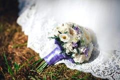 Ramo colorido de la boda hermosa en hierba y el vestido para la novia Fotos de archivo