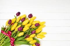 Ramo colorido de los tulipanes adornado con la cinta roja en el fondo de madera blanco Tarjeta de felicitación Copie el espacio Fotografía de archivo libre de regalías