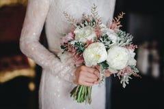 ramo con las flores blancas y rosadas en las manos del ` s de la novia foto de archivo libre de regalías