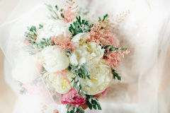 ramo con las flores blancas y rosadas en las manos del ` s de la novia foto de archivo