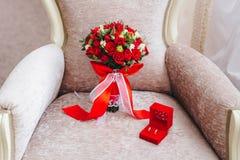 ramo con las flores rojas con los anillos fotografía de archivo libre de regalías