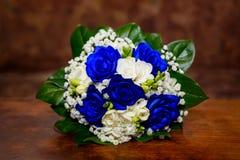 Ramo con las rosas blancas y azules en fondo marrón Imagen de archivo libre de regalías