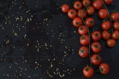 Ramo da cereja dos tomates, no fundo preto Imagem de Stock Royalty Free