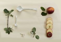 Ramo da colher, da maçã e de maçã de árvore da porcelana com flores em uma tabela branca Fotografia de Stock