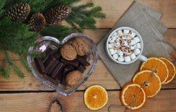 Ramo de árvore do Natal, café, marshmallow, nozes e chocolate em uma tabela de madeira Vista de acima Cartão do Natal e do ano no Fotos de Stock