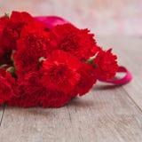 Ramo de claveles rojos en fondo de madera Foto de archivo libre de regalías
